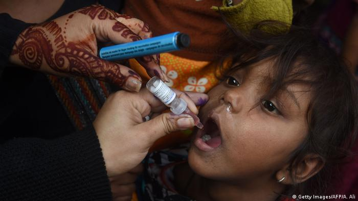 A Pakistani health worker administers polio vaccine drops to a child during a polio vaccination campaign in Lahore