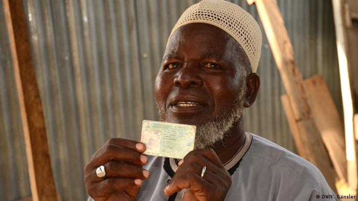 A man holding up his voter card