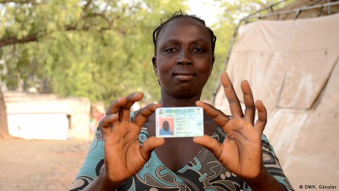 A woman holds up her voter card