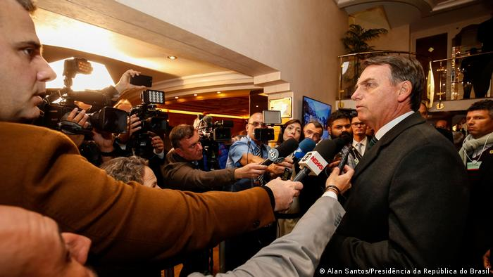 O presidente Jair Bolsonaro conversa com uma multidão de jornalistas