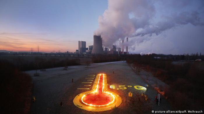 Greenpeace activists have made a thermometer of flames in front of a coal-fired power station