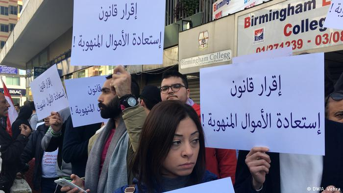 Protesters in Lebanon carrying signs