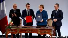 German Chancellor Angela Merkel, French President Emmanuel Macron, French Foreign Minister Jean-Yves Le Drian and German Foreign Minister Heiko Maas attend the signing of a new agreement