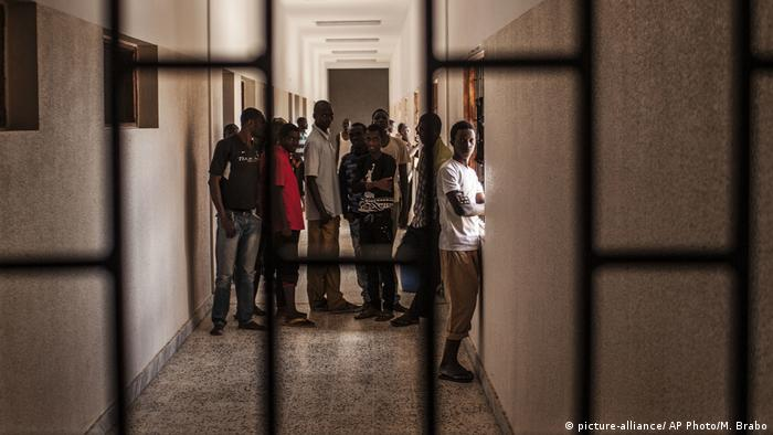Migrants stand in a hall at a detention center for migrants, in the village of Karareem