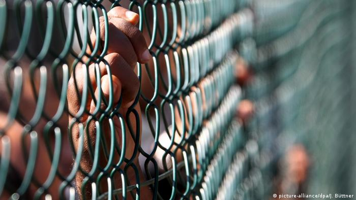 View of a person's hands behind a chin-link fence at a German asylum-seeker center (picture-alliance/dpa/J. Büttner)