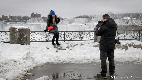 Tourists wrapped up in their winter layers pose for a photo in front of the frozen Niagara Falls. (Reuters/M. Doiron)