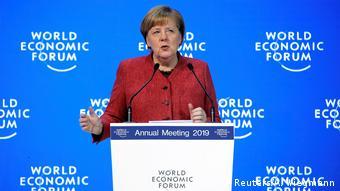 Merkel speaks from a podium at WEF in Davos (Reuters/A. Wiegmann)