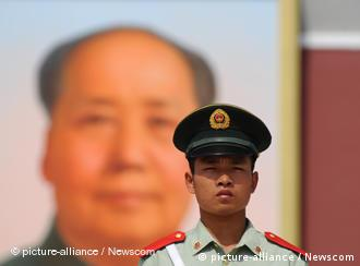 A paramilitary policeman stands by the portrait of Mao Zedong on the Tiananmen Gate in Beijing Sunday Sept. 13, 2009. Photo via Newscom Picture-Alliance