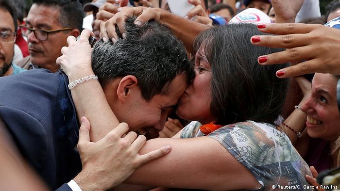 Женщина в толпе целует Хуана Гуайдо