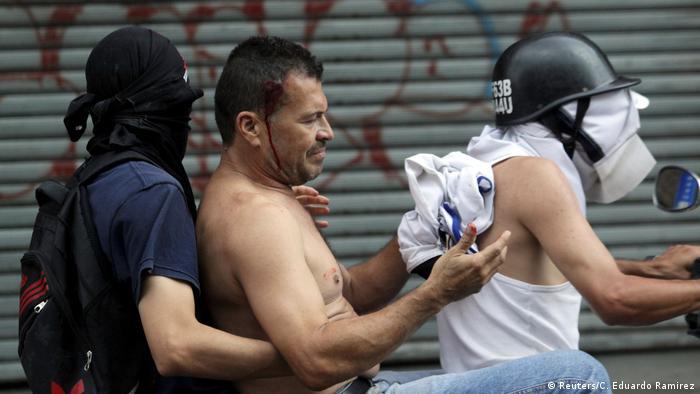 Un manifestante en Caracas es llevado en motocicleta a un lugar seguro.