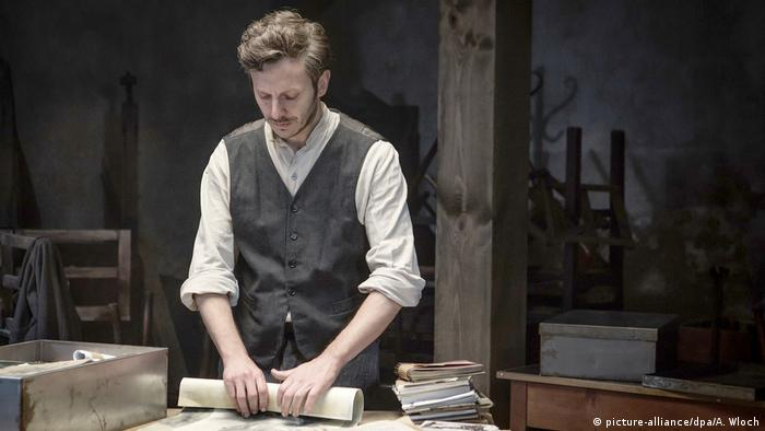 film still from Who will write our history, a man standing at a table, rolling a document