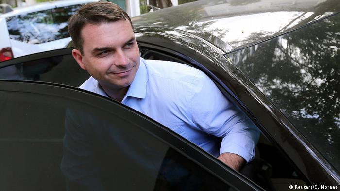 Flávio Bolsonaro sorri ao sair de um carro negro