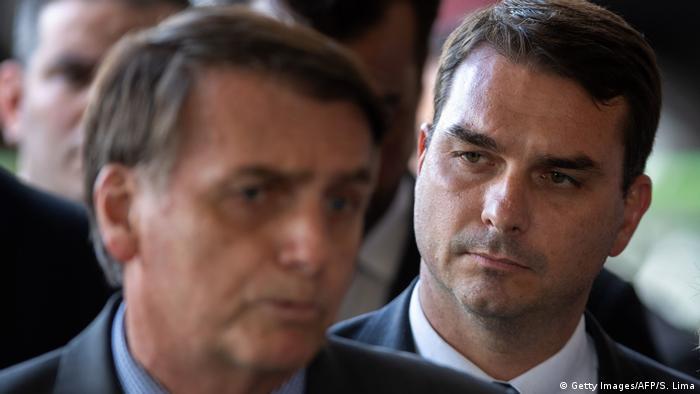 Flávio Bolsonaro, e à frente, seu pai, o presidente Jair Bolsonaro