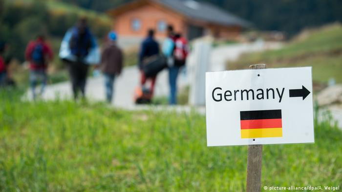Syrian refugees walk past a sign reading Germany (picture-alliance/dpa/A. Weigel)