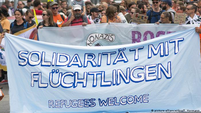 A banner is held up at a demo against the AfD in northeastern German reading refugees welcome