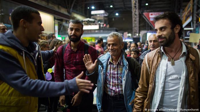 Homem estende a mão para cumprimentar dois homens que passam em estação de trem
