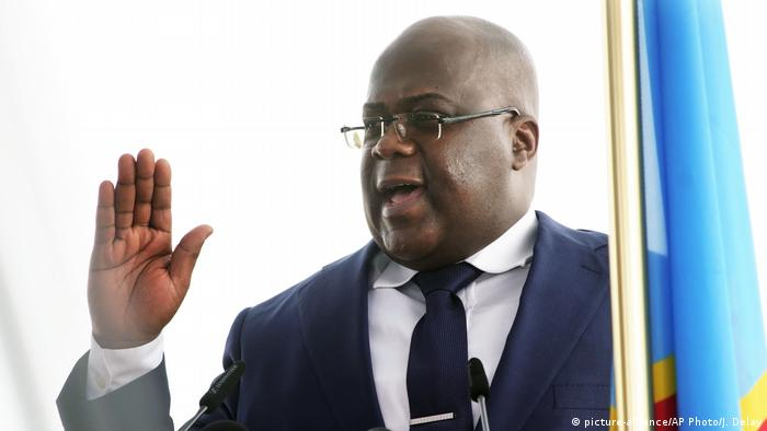 Felix Tshisekedi, standing next to Congo's flag, raises his hand at his swearing in
