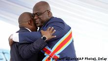 Congolese President Felix Tshisekedi, right, hugs outgoing president Joseph Kabila after being sworn in in Kinshasa, Democratic Republic of the Congo, Thursday Jan. 24, 2019. Tshisekedi won an election that raised numerous concerns about voting irregularities amongst observers as the country chose a successor to longtime President Kabila. (AP Photo/Jerome Delay)  