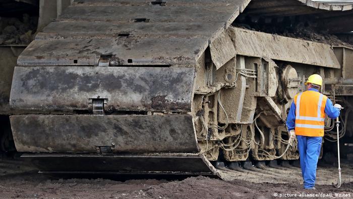 Рабочий стоит рядом с гусеницами роторного экскаватора