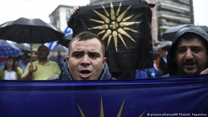 Greek protesters holding up flags of the Vergina Sun