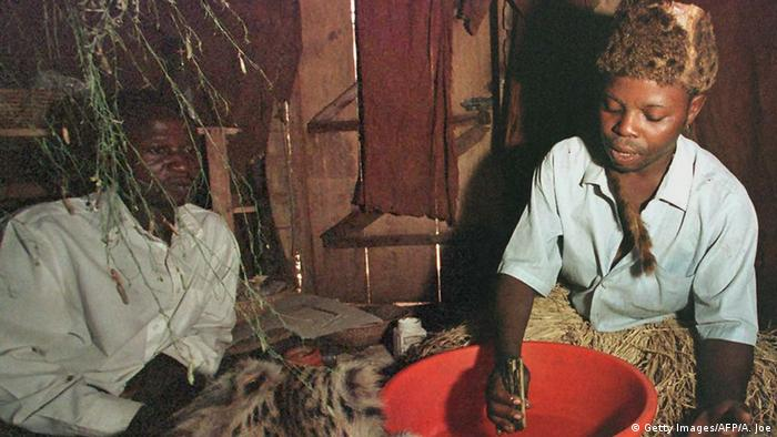 a traditional healer wearing a grass skirt and an animal skin hat sits in his hut with another man