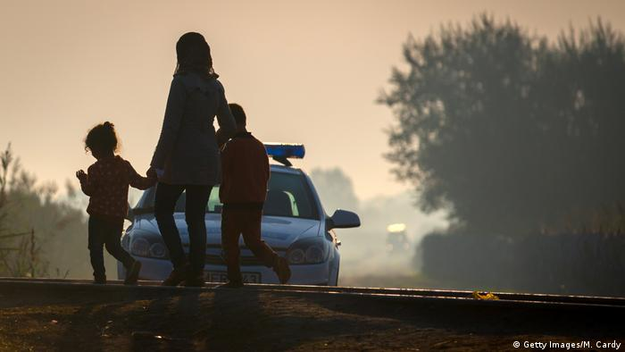 Migrants pass a Hungarian police patrol car parked at the border from Serbia into Hungary