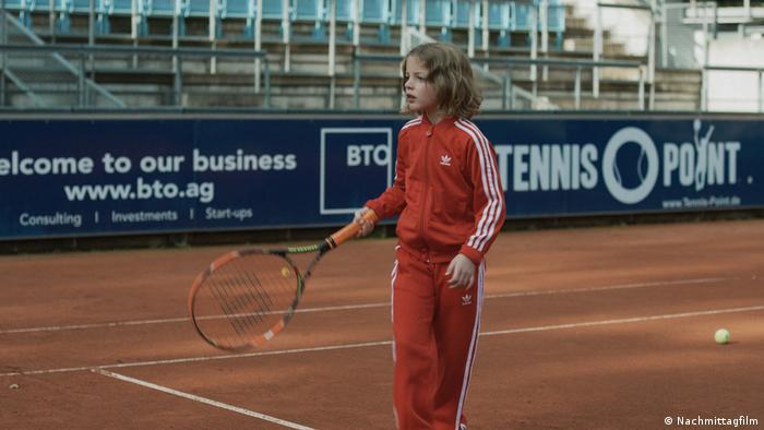 Filmszene aus Ich war zuhause, aber zeigt ein Kind im Trainingsanzug auf einem Tennisplatz (Nachmittagfilm)
