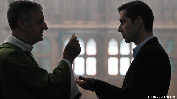 still from the film Grâce à Dieu shows a man taking Communion from a priest (Jean-Claude Moireau)