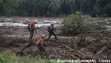 Firefighters search the mud, after a dam collapse near Brumadinho, Brazil, Saturday, Jan. 26, 2019. Rescuers in helicopters on Saturday searched for survivors while firefighters dug through mud in a huge area in southeastern Brazil buried by the collapse of a dam holding back mine waste, with at least nine people dead and up to 300 missing. (AP Photo/Leo Correa)  