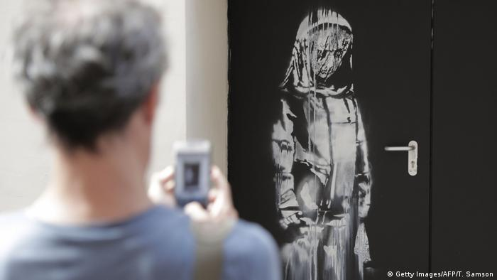 A man photographs a Banksy work (Getty Images/AFP/T. Samson)