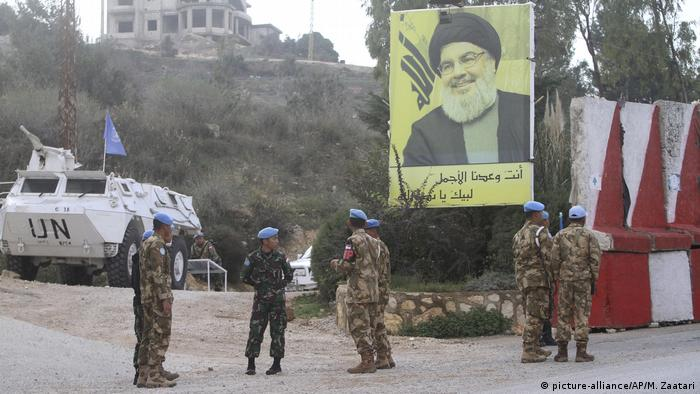 UN peacekeepers in front of a poster of Hezbollah leader Sheik Hassan Nasrallah