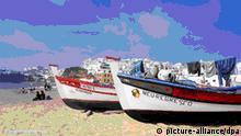 Am Hausstrand von Albufeira, Praia dos Pescadores, liegen wie in alten Zeiten buntbemalte Fischerboote am Strand, zwischen denen sich Touristen auf ihren Handtüchern der Sonne entgegenstrecken. Aufnahme vom 14.10.2003.