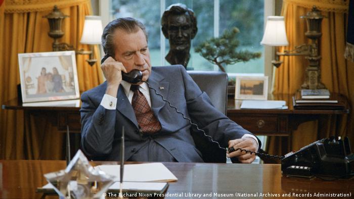 US-Präsident Richard Nixon sitzt am Schreibtisch und telefoniert, im Hintergrund steht eine Lincoln-Büste