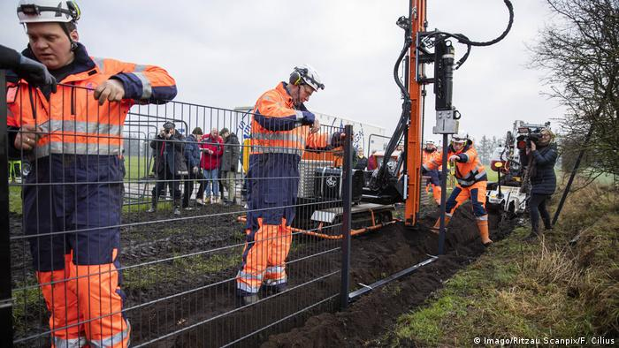 Danish workers install a border fence with Germany