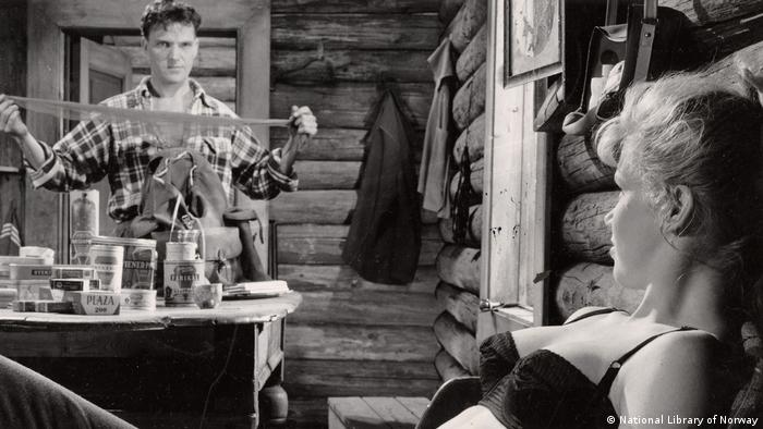 Film still from The Wayward Girl shows woman in bra and man holding nylons (National Library of Norway)