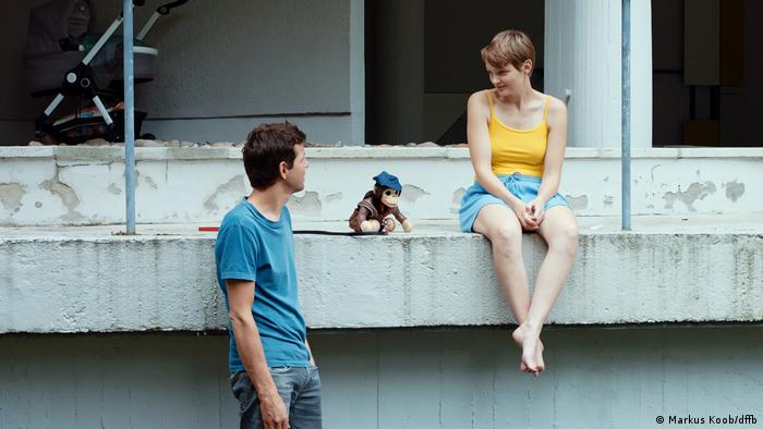 A young man and woman sit in a construction site with a toy monkey between them in a film still from The Components of Love (Markus Koob/dffb)