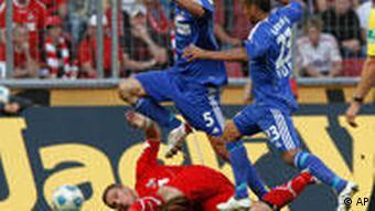 Kölns Podolski verliert den Kampf um den Ball gegen die beiden Leverkusener Spieler Friedrich und Vidal (AP Photo/Hermann J. Knippertz)