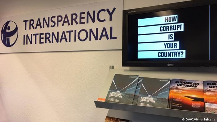 A sign reading Transparency International next to a computer screen with the question How corrupt is your country? (DW/C.Vieira Teixeira)
