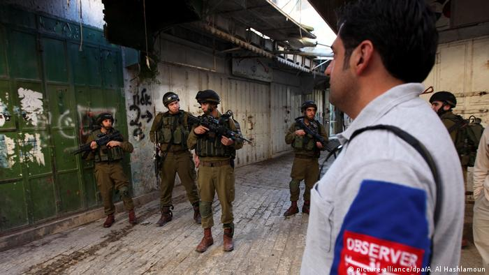 A TIPH observer watches Israeli soldiers in Hebron