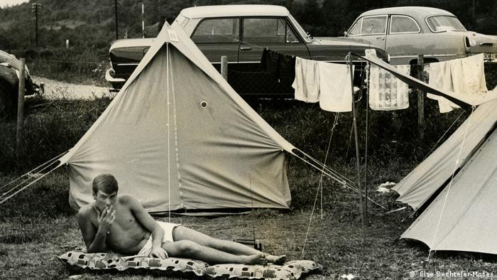 Man in swim trunks lying on an air mattress at a campsite ( Else Bechteler-Moses)