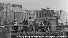 British rock group the Beatles performing their last live public concert on the rooftop of the Apple Organization building for director Michael Lindsey-Hogg's film documentary, 'Let It Be,' on Savile Row, London, UK, 30th January 1969; singer-songwriters Paul McCartney and John Lennon (1940 - 1980) perform at their microphones, and guitarist George Harrison (1943 - 2001) on the right. Lennon's wife Yoko Ono sits at right. (Photo by Evening Standard/Hulton Archive/Getty Images)