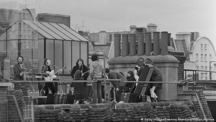 Großbritannien 1969 | The Beatles' rooftop concert, Die Beatles stehen auf dem Dach ihres Firmensitzes, vlnr: Paul, John, George und ein paar Zuschauer, ganz rechts ein Kameramann, der die Szene filmt