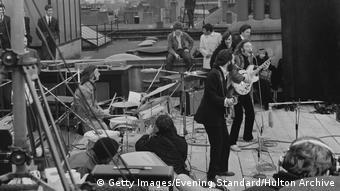 Großbritannien 1969 | The Beatles' rooftop concert, Die Beatles auf dem Dach, das Bild zeigt die Band von der Seite, Ringo sitzt hinter den anderen Musikern, im Hintergrund die Dächer der Umgebung