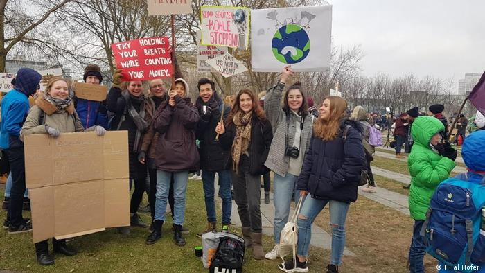 Eine Gruppe junger Menschen auf einer Wiese, sie halten Schilder in die Luft