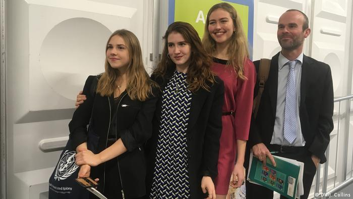 Drei junge Frauen und ein Mann vor einer weißen Wand, sie lächeln in die Kamera