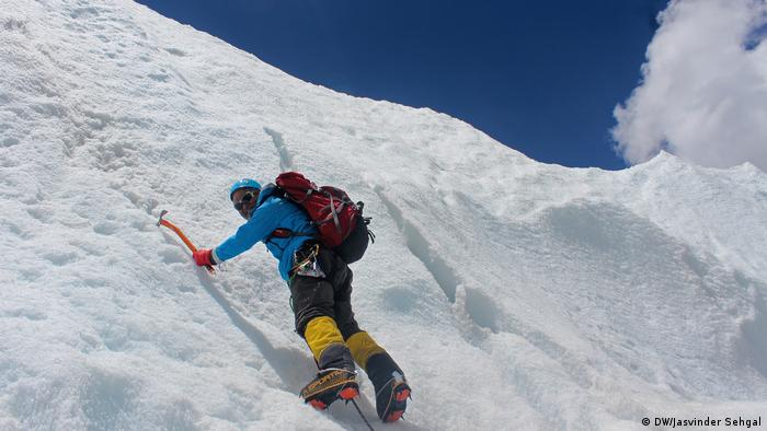 A man is climbing in the Himalayas on a frozen mountain face on the way to Mount Everest. Just surviving at this altitude is a challenge and carrying trash down from the summit is often not a priority.