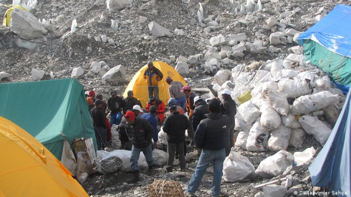 Men are standing at Everest base camp in the high Himalayas, surrounded by tents and bags of trash. The site has been called the world's highest rubbish dump.