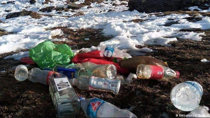 bottles, plastic and glass, cans and other trash in the snow on the slopes of Mount Everest