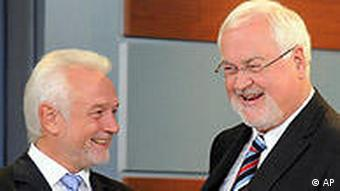 Wolfgang Kubicki of the Free Democratic Party, FDP, left, and state governor Peter Harry Carstensen, of the Christian Democratic Party, CDU, right, laugh together, after the elections in the German state of Schleswig-Holstein in Kiel, northern Germany, Sunday, Sept. 27, 2009. (AP Photo/Fabian Bimmer)