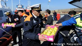 A member of the Italian Coast Guard carries a crate of apples to be brought on board the Sea Watch 3 vessel (Reuters/G. Mangiapane)